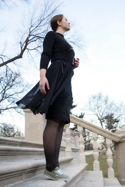 Cait posing in a black outfit that represents her modest style.