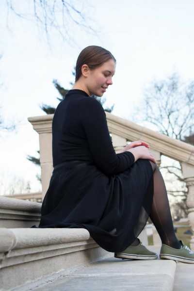 Cait sitting on arboretum steps in black, modest, ballet-inspired outfit.