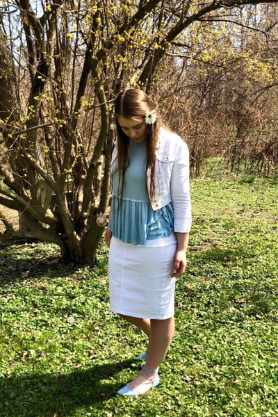 Caitlyn in a white jean skirt, blue peplum top, and white jean jacket.